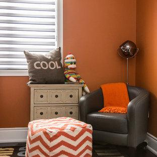 Idées déco pour une chambre d'enfant de 4 à 10 ans contemporaine de taille moyenne avec un mur orange et un sol en bois foncé.
