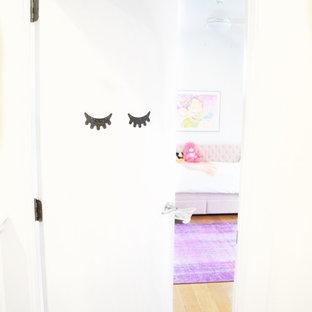 Ispirazione per una grande cameretta per bambini da 4 a 10 anni eclettica con pareti bianche, parquet chiaro e pavimento marrone