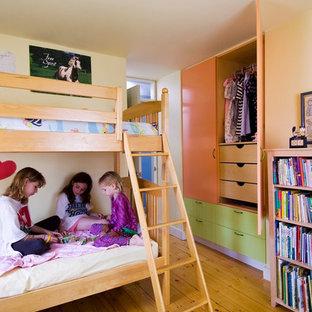 Ispirazione per una cameretta per bambini da 4 a 10 anni bohémian con pareti beige e pavimento in legno massello medio