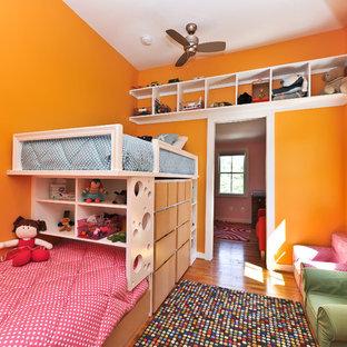 Inredning av ett modernt flickrum kombinerat med sovrum och för 4-10-åringar, med orange väggar och mellanmörkt trägolv