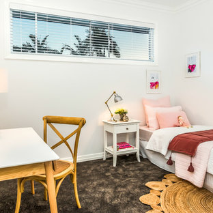 This is an example of a beach style kids' room for girls in Townsville with white walls, carpet and black floor.