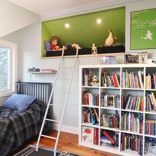 Immagine di una cameretta per bambini contemporanea di medie dimensioni con pareti blu e pavimento in legno massello medio