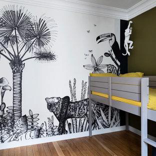 Aménagement d'une chambre d'enfant de 4 à 10 ans contemporaine de taille moyenne avec un mur multicolore et un sol en bois clair.