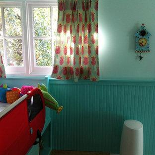 Ispirazione per una cameretta per bambini da 4 a 10 anni stile americano di medie dimensioni con pareti blu e pavimento in legno massello medio