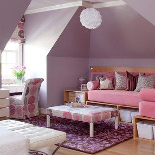 Réalisation d'une grand chambre d'enfant de 4 à 10 ans tradition avec un mur violet et un sol en bois clair.