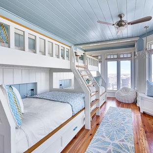 Ejemplo de dormitorio infantil costero con paredes azules y suelo de madera en tonos medios