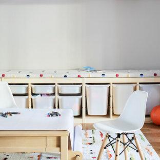 Cette photo montre une chambre d'enfant de 1 à 3 ans moderne de taille moyenne avec un mur beige, un sol en bois brun et un sol marron.