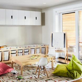 Idée de décoration pour une chambre d'enfant de 1 à 3 ans nordique de taille moyenne avec un mur beige, un sol en bois brun et un sol marron.