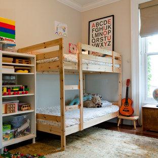Eklektisk inredning av ett könsneutralt barnrum för 4-10-åringar och kombinerat med sovrum, med beige väggar och mörkt trägolv