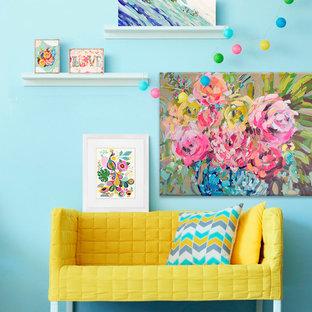 Cette image montre une chambre d'enfant bohème avec un bureau et un mur bleu.