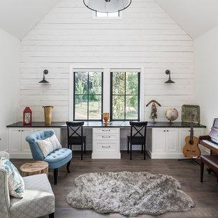 Foto på ett stort lantligt könsneutralt barnrum kombinerat med skrivbord, med vita väggar, mörkt trägolv och brunt golv