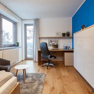Ejemplo de dormitorio infantil actual, de tamaño medio, con paredes azules y suelo de contrachapado