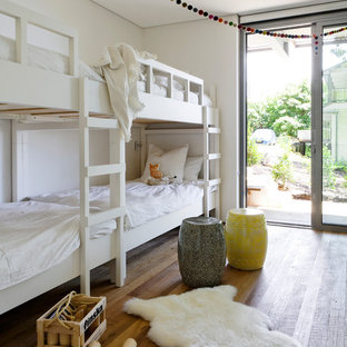 Design ideas for a contemporary gender-neutral kids' bedroom in Sydney with white walls, medium hardwood floors and brown floor.