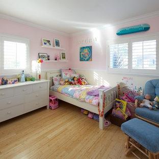 Cette photo montre une chambre d'enfant tendance avec un sol en bambou et un mur rose.