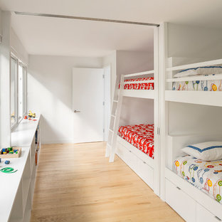 Kids' room - contemporary gender-neutral light wood floor kids' room idea in Portland Maine with white walls