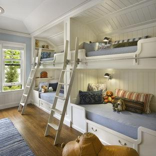 Elegant gender-neutral medium tone wood floor kids' room photo in Chicago with blue walls