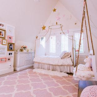 Exempel på ett stort modernt flickrum kombinerat med sovrum och för 4-10-åringar, med vita väggar och mellanmörkt trägolv