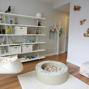 Mid-sized scandinavian gender-neutral kids' room in New York with grey walls and light hardwood floors.