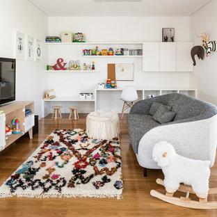Mid-sized scandinavian gender-neutral kids' study room in Perth with white walls, medium hardwood floors and brown floor.