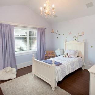 Immagine di una cameretta per bambini da 4 a 10 anni american style di medie dimensioni con pareti viola e pavimento in legno massello medio