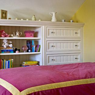 Ejemplo de dormitorio juvenil clásico con paredes amarillas