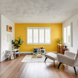 Transitional gender-neutral medium tone wood floor and brown floor kids' room photo in Los Angeles with yellow walls
