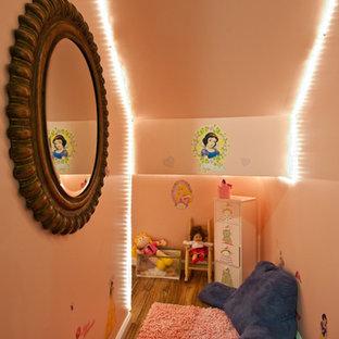 Esempio di una grande cameretta per bambini con pareti beige e pavimento in legno massello medio