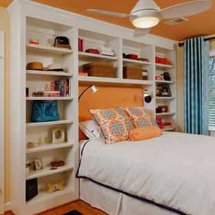 Modelo de dormitorio infantil clásico renovado con parades naranjas y suelo de madera en tonos medios