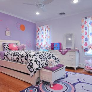 Exempel på ett stort modernt flickrum kombinerat med sovrum och för 4-10-åringar, med lila väggar och mellanmörkt trägolv