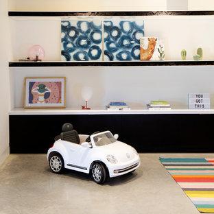 Modern inredning av ett stort könsneutralt barnrum kombinerat med lekrum och för 4-10-åringar, med vita väggar, betonggolv och grått golv