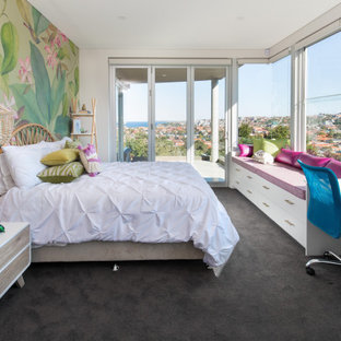 This is an example of a contemporary kids' room for girls in Sydney with carpet, grey floor and multi-coloured walls.