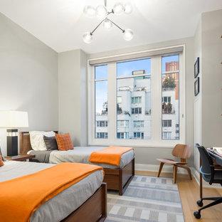 Foto de dormitorio infantil actual con parades naranjas, suelo de madera clara y suelo marrón