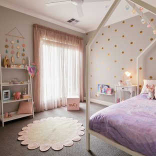 This is an example of a transitional kids' bedroom for kids 4-10 years old and girls in Melbourne with grey walls, carpet and grey floor.