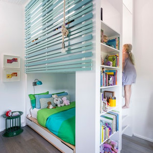 Example of a trendy girl medium tone wood floor and gray floor kids' bedroom design in Los Angeles with white walls