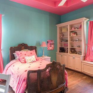 Ispirazione per una cameretta per bambini da 4 a 10 anni mediterranea con pareti blu e pavimento in legno massello medio