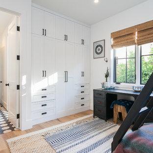Modelo de dormitorio infantil de estilo de casa de campo con paredes blancas, suelo de madera en tonos medios y suelo beige