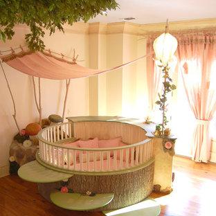 Esempio di una cameretta per bambini da 4 a 10 anni eclettica di medie dimensioni con pareti beige e pavimento in legno massello medio