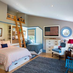 Modelo de dormitorio infantil de estilo de casa de campo con paredes grises, suelo de madera en tonos medios y suelo marrón