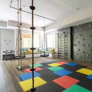 Idéer för ett mycket stort modernt könsneutralt barnrum kombinerat med lekrum och för 4-10-åringar, med svarta väggar, mörkt trägolv och brunt golv