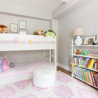 Photo of a classic toddler's room for girls in New York with grey walls, medium hardwood flooring and brown floors.