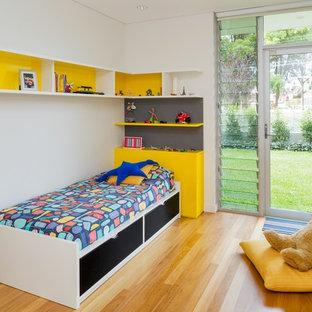 Exemple d'une chambre d'enfant de 4 à 10 ans tendance avec un mur blanc et un sol en bois brun.