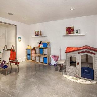 Idéer för mellanstora funkis könsneutrala barnrum kombinerat med lekrum och för 4-10-åringar, med vita väggar och betonggolv