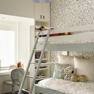 Trendy medium tone wood floor and brown floor kids' bedroom photo in New York with white walls