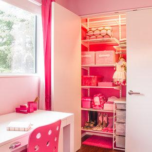 Immagine di una cameretta per bambini da 4 a 10 anni moderna di medie dimensioni con pareti rosa e parquet scuro