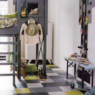 Modern inredning av ett mellanstort könsneutralt barnrum, med vita väggar, linoleumgolv och flerfärgat golv