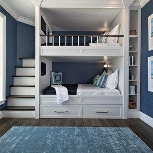 Inredning av ett maritimt könsneutralt barnrum kombinerat med sovrum, med blå väggar, mörkt trägolv och brunt golv