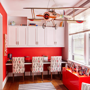 Cette photo montre une chambre neutre de 4 à 10 ans chic de taille moyenne avec un bureau, un sol en bois brun, un mur rouge et un sol marron.