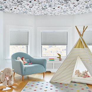 Imagen de dormitorio infantil de 1 a 3 años, clásico renovado, grande, con paredes blancas, suelo de madera clara y suelo marrón