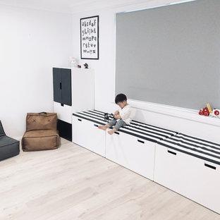 Idee per una cameretta per bambini da 1 a 3 anni moderna di medie dimensioni con pareti bianche, pavimento in laminato e pavimento beige