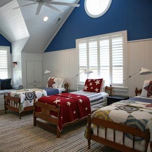 Aménagement d'une grand chambre d'enfant bord de mer avec un mur bleu, un sol en bois brun, un sol marron, un plafond voûté et boiseries.